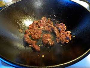 Beef cooking in cast iron wok